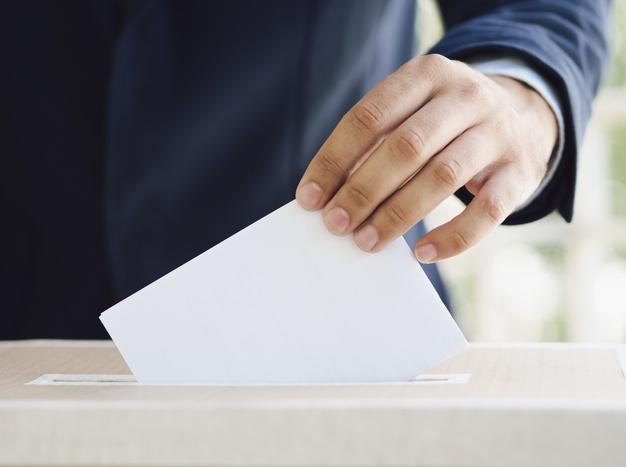 homem colocando voto em urna