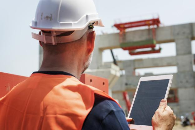 trabalhador olhando obra com EPI e um tablet em mãos